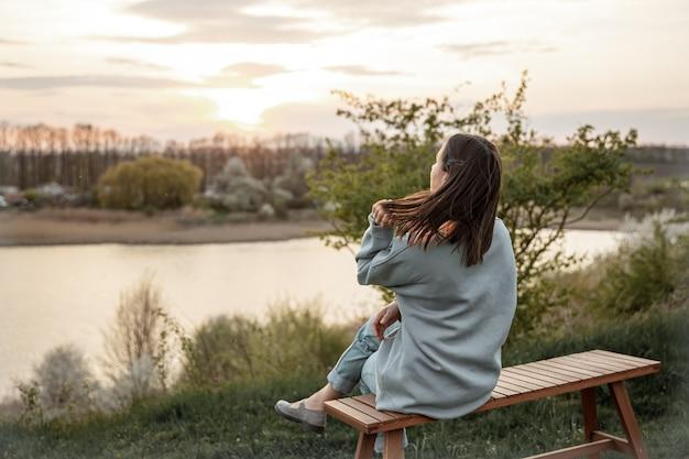 Der blick von hinten auf das mädchen blickt auf den sonnenuntergang, das auf einer bank sitzt