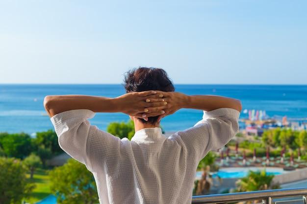 Der blick von hinten eine frau auf dem balkon stehend. sommermorgen.