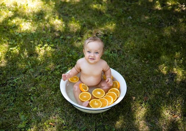 Der blick von oben. ein kleines schönes mädchen sitzt in einer orangenwanne auf dem grünen gras und schaut in die kamera