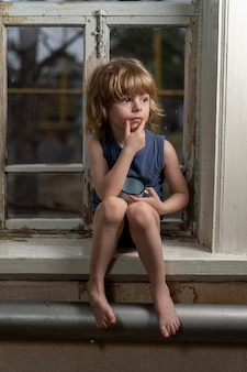 Der blonde junge sitzt mit einem verwirrten blick auf einer schäbigen holzfensterbank