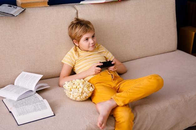 Der blonde junge spielt mit dem gamepad anstatt mit dem unterricht und isst popcorn.