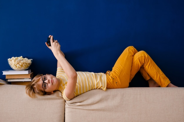 Der blonde junge spielt mit dem gamepad anstatt mit dem unterricht Premium Fotos