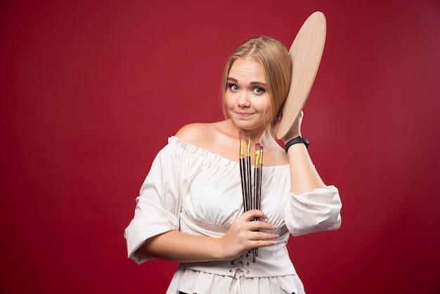 Der blonde künstler hält eine palette und pinsel und sieht positiv und engagiert aus.