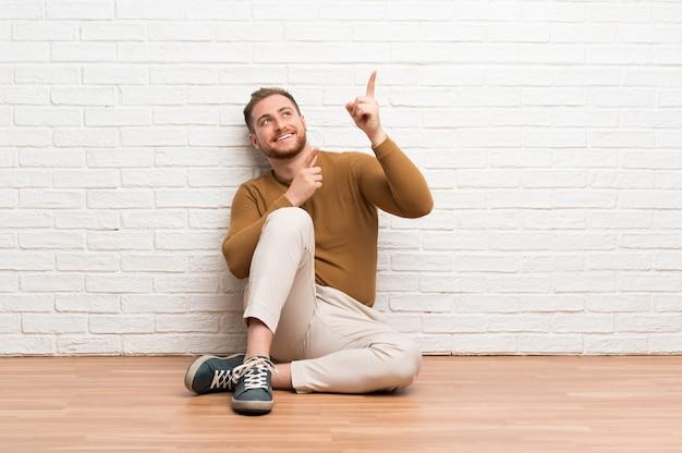 Der blonde mann, der auf dem boden zeigt mit dem zeigefinger sitzt, eine großartige idee