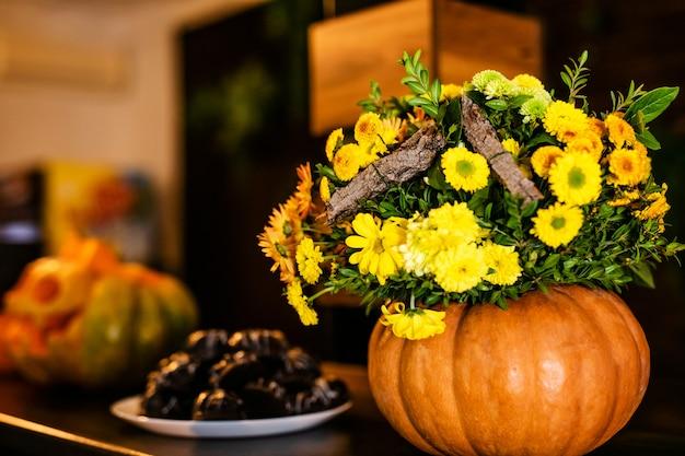 Der blumenstrauß von herbstblumen im kürbis auf der feier von halloween