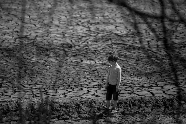 Der boden ist trocken und rissig. die wüste, der hintergrund der globalen erwärmung. der junge steht in der mitte.