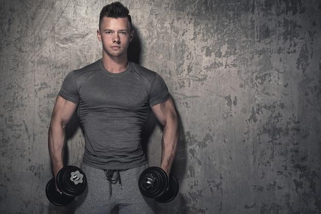 Der bodybuilder, der bizeps tut, kräuselt sich mit dummköpfen