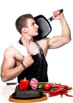 Der bodybuilder-koch bereitet ein mittagessen mit gemüse und fleisch zu.