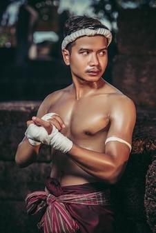 Der boxer saß auf dem stein, band das band um seine hand und bereitete sich auf den kampf vor.