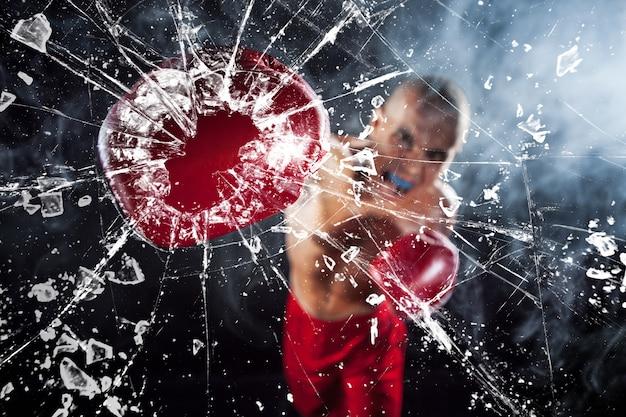 Der boxer zerquetscht ein glas. der junge männliche athlet kickboxen auf einem blauen rauch