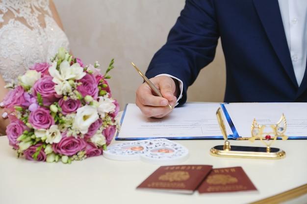 Der bräutigam an einem hochzeitstag setzt eine unterschrift. hochzeitszeremonie.