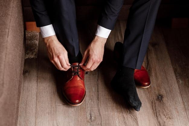 Der bräutigam band die schnürsenkel an den schuhen ganz nah. geschäftsmann hängt schuhe drinnen im hotelzimmer. mans hände und ein paar leder herrenschuhe. treffen des bräutigams. geschäftsmannmorgen.