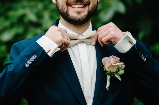 Der bräutigam befestigt die krawatte mit ihrer handfliege in einem anzug mit knopfloch an der jacke