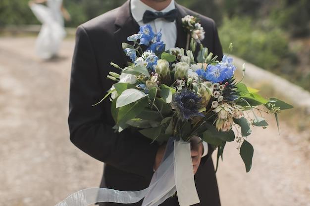 Der bräutigam begegnet der braut mit einem blumenstrauß