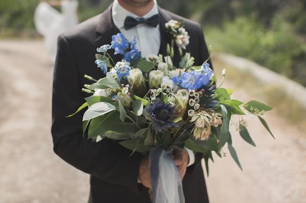 Der bräutigam begegnet der braut mit einem blumenstrauß.