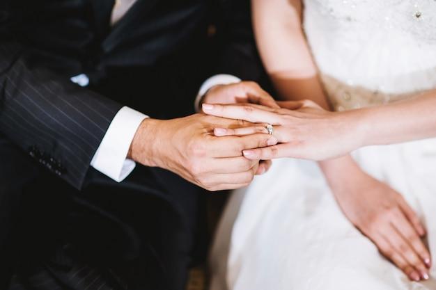Der bräutigam, der den ehering auf den finger der braut setzt