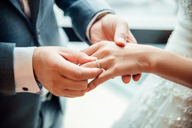 Der bräutigam, der sorgfältig einen ehering zur braut trägt
