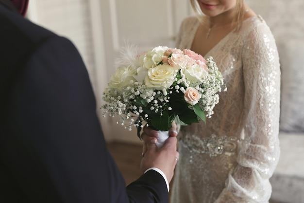 Der bräutigam gibt der braut einen strauß schöner blumen.