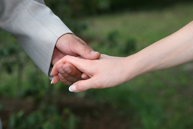 Der bräutigam hält die braut an der handnahaufnahme