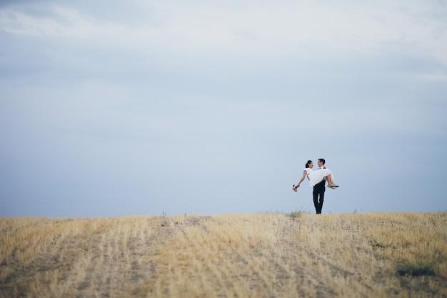 Der bräutigam hält die braut auf dem feld in den armen. hochzeit
