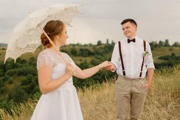 Der bräutigam hält die braut bei der hochzeit an der hand gegen schöne landschaft