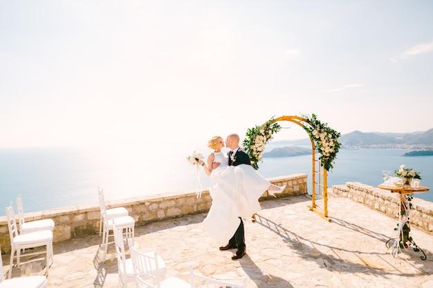 Der bräutigam hält die braut in einem weißen kleid mit einem blumenstrauß in den armen, während er auf dem steht