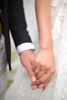 Der bräutigam hält die hand der braut am finger eines goldenen eherings in der hand