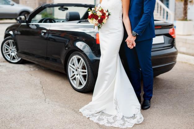 Der bräutigam hält die hand der braut mit einem blumenstrauß, während er auf den pflastersteinen dagegen steht