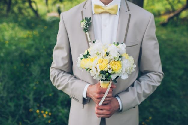 Der bräutigam hält einen hochzeitsblumenstrauß