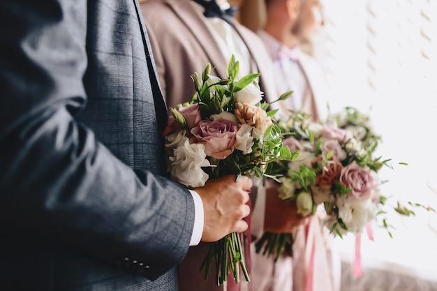 Der bräutigam hält einen hochzeitsstrauß in seinen händen
