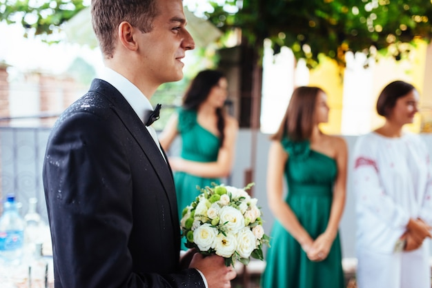 Der bräutigam hält einen hochzeitsstrauß