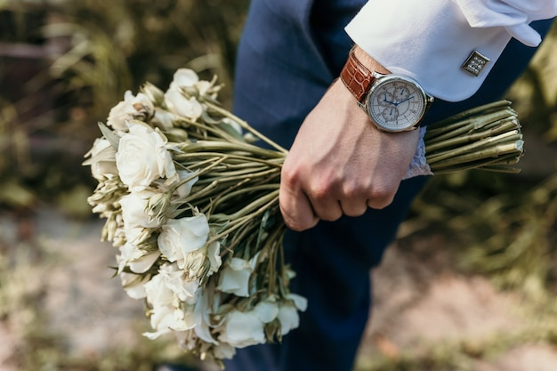 Der bräutigam hält in seiner hand einen weißen blumenstrauß der brautnahaufnahme. eine uhr ist auf der hand getragen. manschettenknopf am ärmel.