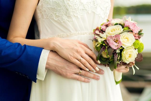 Der bräutigam hält sanft die hände der braut