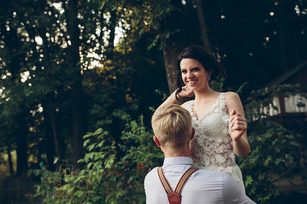 Der bräutigam hält seine braut irgendwo in der natur in den armen