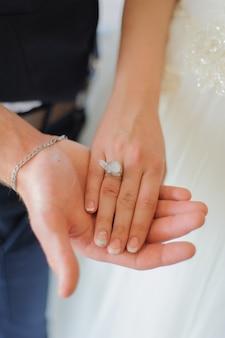 Der bräutigam hält seine geliebte an der hand. die braut hat keinen quarzring in der hand