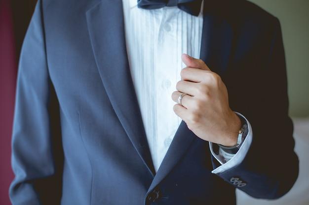 Der bräutigam hat seinen blauen anzug erwischt, dass sein finger einen ehering hat