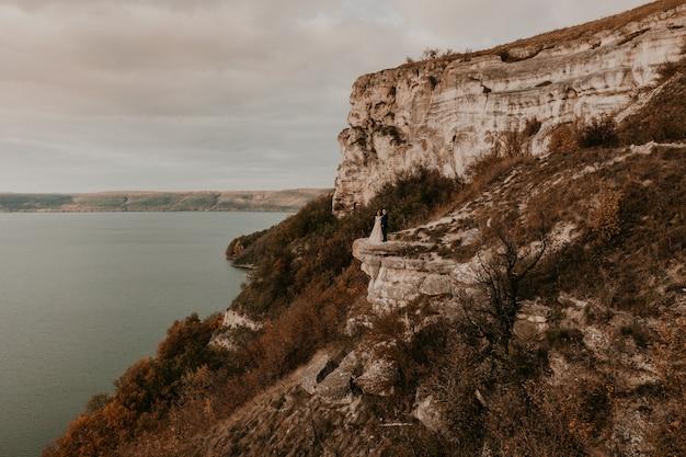 Der bräutigam im anzug und die braut in einem kleid stehen auf einer steinklippe über dem fluss