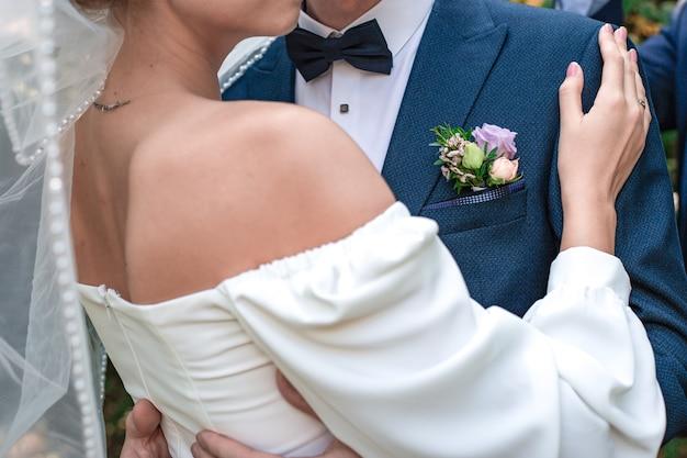 Der bräutigam im blauen anzug und die braut im weißen kleid umarmen sich zusammen. die hand einer frau mit einem ring auf der schulter eines mannes. hochzeit, verlobung. liebes- und beziehungskonzept.