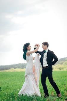 Der bräutigam im braunen anzug und die braut im elfenbeinfarbenen kleid auf einer grünen wiese, die sich in die ferne gegen den himmel zurückzieht