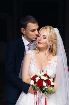 Der bräutigam im stylischen anzug umarmt die braut von hinten