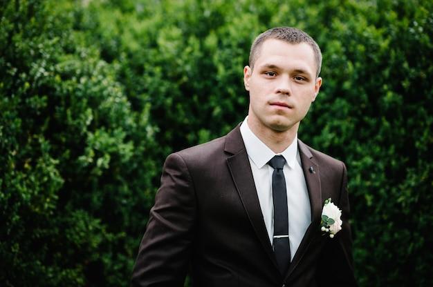 Der bräutigam in anzug und krawatte mit boutonniere oder knopfloch an der jacke steht auf dem grün im garten, park.