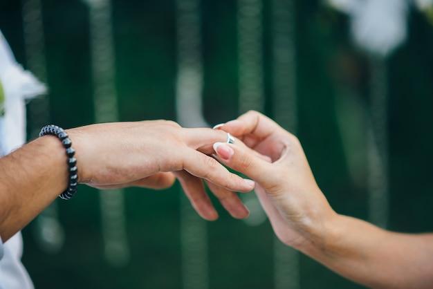 Der bräutigam in einer uhr und einem anzug legt den ehering an den finger der braut