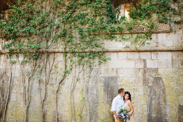 Der bräutigam küsst zärtlich die braut in einem schönen kleid in pastellfarben