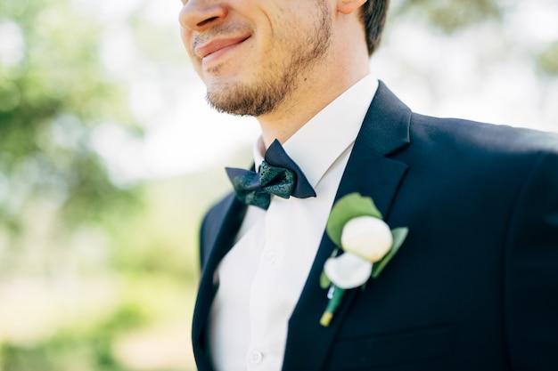 Der bräutigam lächelt im hochzeitsanzug mit fliege und boutonniere