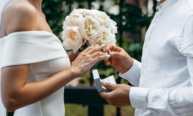 Der bräutigam legt den ehering an den finger der braut