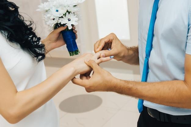 Der bräutigam legt den ring während der hochzeit an die braut. liebe und heirat. hochzeitszeremonie.