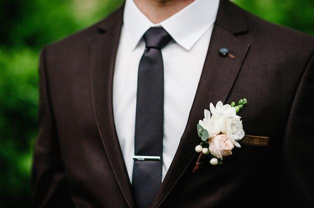 Der bräutigam mit boutonniere oder knopfloch an der jacke.
