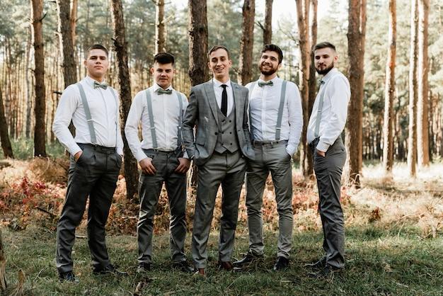 Der bräutigam mit freunden hält die hände in den taschen und schaut in die kamera