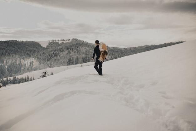 Der bräutigam nahm seine braut auf die schulter und trug sie durch den schnee weg