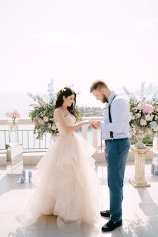 Der bräutigam steckt den ring während der hochzeitszeremonie auf den finger der braut vor dem hintergrund von